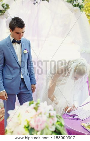 Bride is signing up a wedding paper