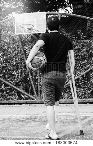 Man Standing With Broken Leg In Plaster Cast Using Crutches