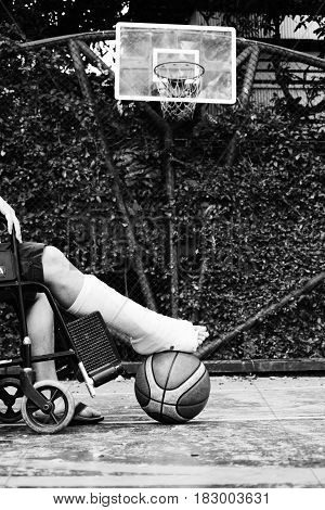 man sitting on wheel chair with broken leg in Plaster cast at basketball court