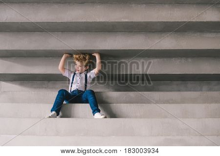 Little boy sitting on a staors and keep the ceiling