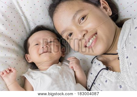 cute Asian baby laying on bed with mother just woke up