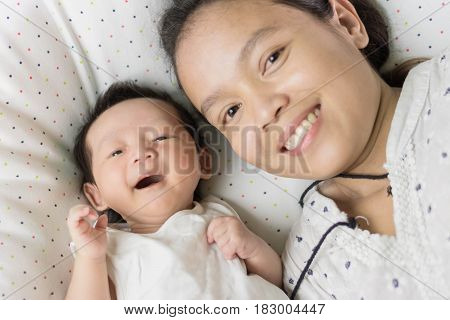 Cute Asian Baby Laying On Bed With Mother