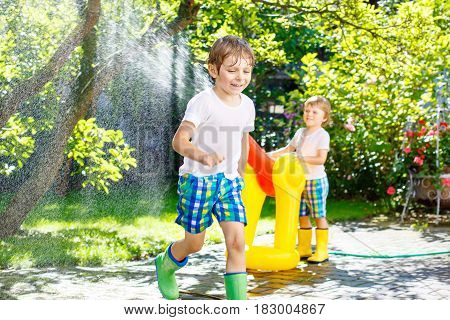 Two little kids boys playing with a garden hose sprinkler on hot and sunny summer day. Children having fun with sprinkling water, drops rain. Outdoors leisure wth water for friends. Rain rubber boots