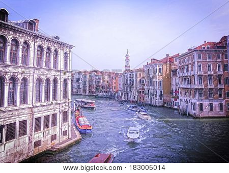 The toned image in retro stile. Beautiful view from Grand Canal on colorful facades of old medieval houses in Venice, Italy at sunset