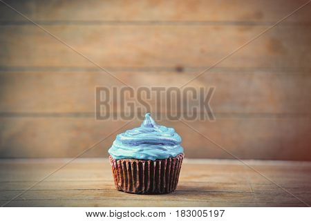 photo of tasty delicious cupcake on the wonderful brown wooden background