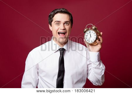 Portrait Of Handsome Young Man With Alarm Clock On The Wonderful Burgundy Studio Background