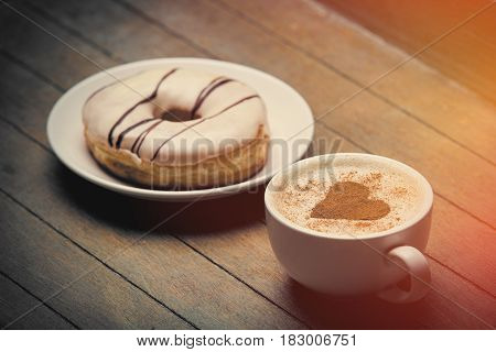 Photo Of Glazed Donut And Cup Of Coffee On The Wonderful Brown Wooden Background