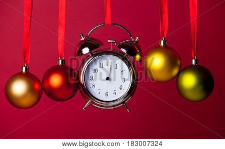 photo of cute baubles and alarm clock on the wonderful red studio background