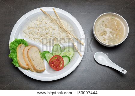 Disposable plastic food plate on black table. White plate with rice meat and vegetables. Soup with sprouts. Spoon and bamboo chopsticks. Healthy take-away concept