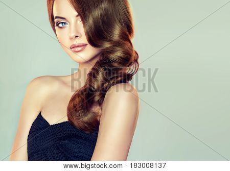 Brunette  girl with long  and  volume shiny wavy hair .  Beautiful  model with curly hairstyle