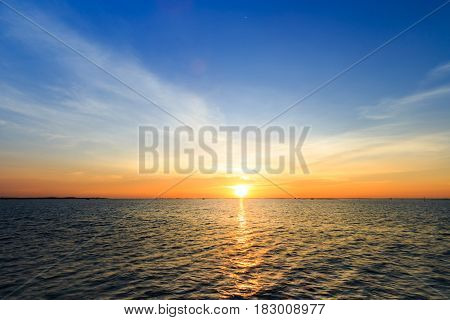 Sunset Over Sea Shore And Silhouette Shell Farm