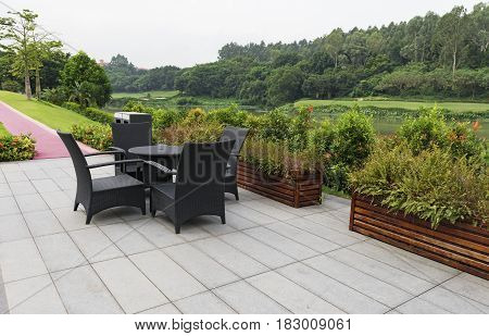 rattan sofa and table set in a garden with lake