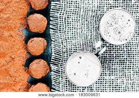 Homemade chocolate truffles and two cups of cocoa drink on burlap. Top view