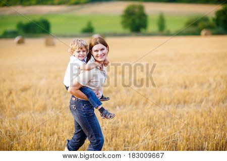 Happy family enjoying sunset in wheat field. Beautiful young woman with adorable toddler kid boy. Mother holding her child, on arms and back on meadow on a sunny evening. Mom and son. Outdoors.