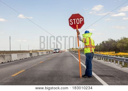 Road construction on the highway Worker holds a stop sign to control the traffic