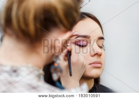 professional makeup artist doing glamour makeup for young girl. Eye makeup. Make-up artist work in her studio. Real people. Backstage photo as visagiste applying makeup