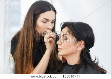 professional makeup artist doing makeup for middle aged women. Girl work in beauty salon. Real people. Visagiste applying eyebrow makeup. Backstage photo. Contouring brows. Eyebrows shaping