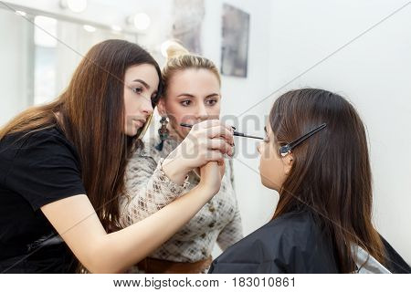 makeup teacher with her student girl. Makeup tutorial lesson at beauty school. Make-up artist work in her studio. Real people. Portrait of visagiste applying makeup on the eyes. Makeup master class