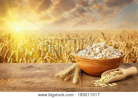 Oat flakes in bowl. Still life ears of oats and oatmeal in bowl on table with ripe cereal field on the background. Healthy eating for diet and vegan. Golden field on sunset