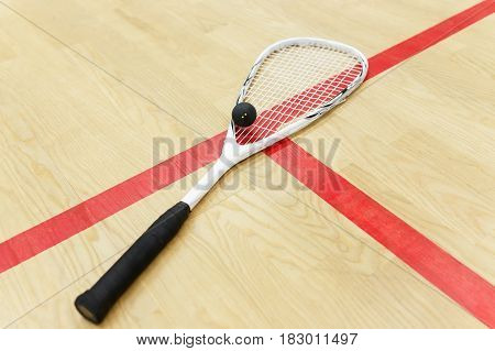 white squash racket and ball on the wooden background. Racquetball equipment on the court near red line. Photo with selective focus