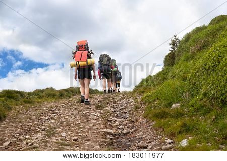 group of hikers with backpacks on  path in the mountains. Active holidays. Tourists trekking on dirt road. Healthy lifestyle, adventure, active leisure tourism and hiking concept