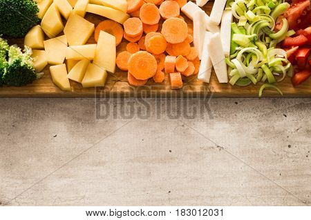Horizontal view of cut vegetables. Copy space on gray stone background. Carrots, broccoli, parsley root, leek, tomato and potatoes.