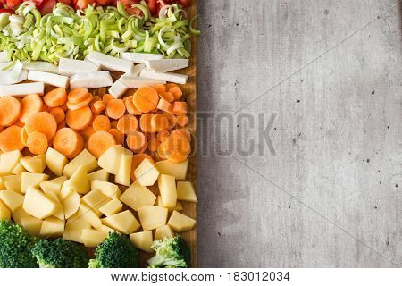 Vertical view of cut vegetables. Copy space on gray stone background. Carrots, broccoli, parsley root, leek, tomato and potatoes.