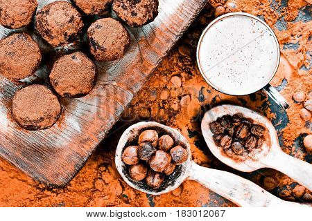 Cocoa powder scattered on black slate with homemade chocolate truffles, coffee beans and nuts in rustic wooden spoons. Top view