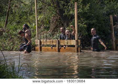 Team Of Men And Women Crossing A River Challenge And Having Fun