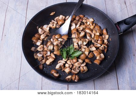 freshly roasted champignons with parsley in the frying pan