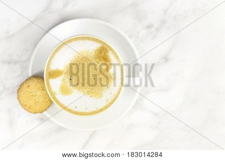 A photo of a cup of coffee with milk with a butter cookie, shot from above on a light texture for copy space