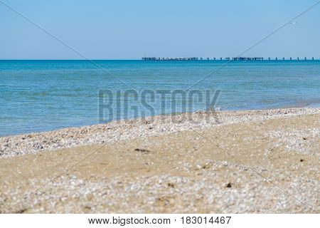 Pier in the black sea in the distance on the background of blue clear Sunny sky.