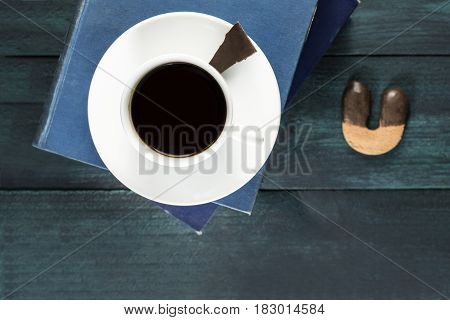 Cup of black coffee, shot from above with old books, a piece of chocolate, and a horseshoe shaped cookie, with copy space. A horizontal design template for a cafe or shop. Selective focus