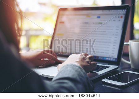 A business woman working and typing on laptop keyboard with mobile phone on table and blur nature background