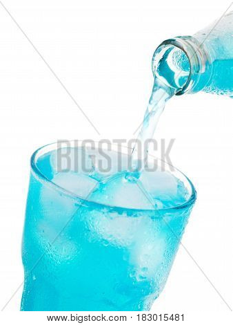 Pouring Blue Soda Into Glass With Ice From Bottle