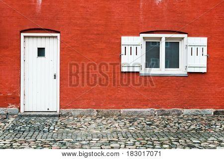 Facade of old red Danish house with white window and door, Copenhagen, Denmark