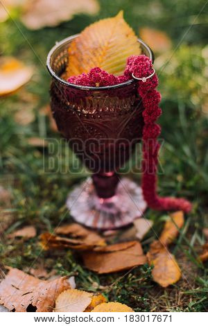bridal ring with autumn leaves in glass cup