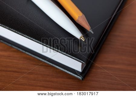 Black Diary, Or Sketchbook With Pen And Pencil On Th Table