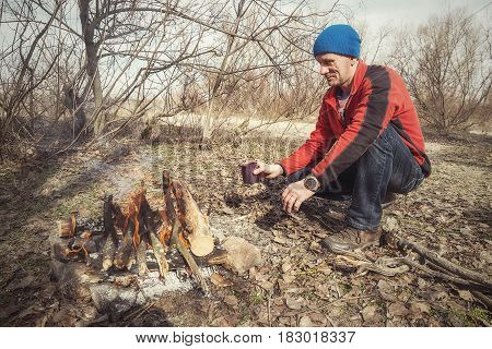 Tired Traveler With A Cup Of Coffee Is Warming Himself By The Campfire
