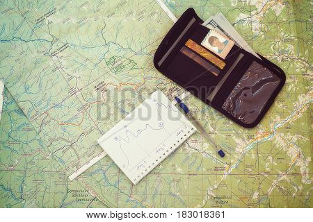 Journey planning - a maps a wallet with credit cards and money a marked route on the map are on the table.Travel and adventure are waiting.