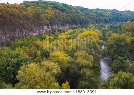 Panorama of the picturesque canyon with rocky walls overgrown with lush thick forest.
