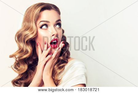 Shocked and surprised girl screaming and  looking to the side presenting  your product . Woman amazed .Beautiful girl  with curly hair and red nails manicure. Expressive facial expressions
