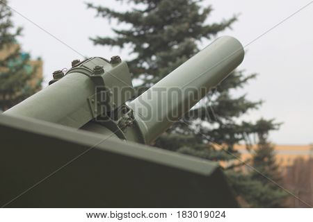 Cannon barrel of powerful green tank with blue sky on background, modern army artillery, military industry