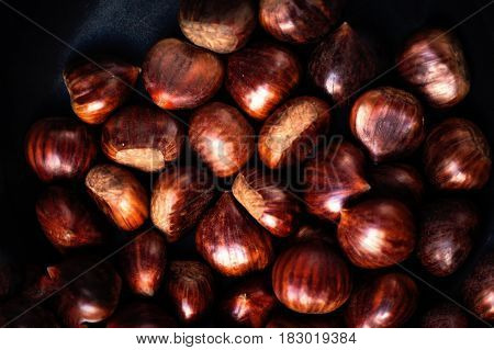 Heap of edible fresh chestnuts on old wooden table. Group of ripe big chestnuts with copy space macro