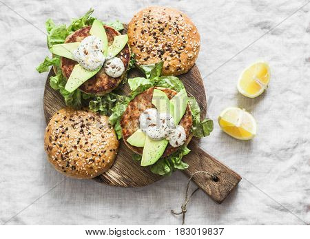 Fish burger. Burgers with tuna avocado and mustard sauce with whole grain homemade buns on wooden cutting board on a light background top view