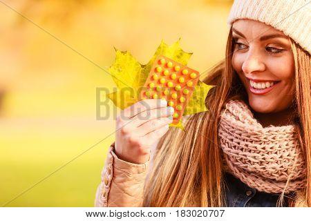 Woman In Autumn Park Holding Vitamins Medicines