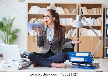 Businesswoman with loudspeaker in office