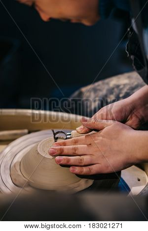 Potter models shape to a clay ware with a tool on a potter's wheel,  handmade work in the potter's studio, vertical photo