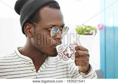 Coffee Time. Confident Fashionable African Male In Hat And Shades Holding Mug, Drinking Fresh Cappuc