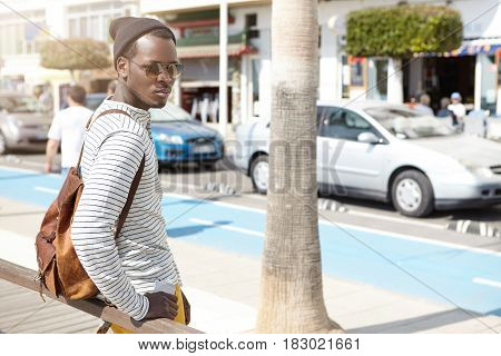 Fashionable Attractive Young Afro-american Traveler In Sunglasses And Hipster Hat Standing At Bus St